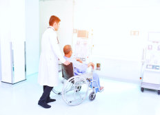 doctor with patient on a wheelchair about to enter a room