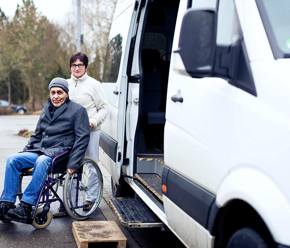 caregiver standing behind an elder man on a wheelchair